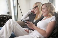 Two girlfriends on a sofa Stock Photography