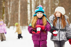 Two girlfriends stand in winter park holding snowballs Stock Images
