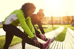 Two girlfriends stretching in sunny park Stock Images