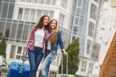 Two girlfriends with suitcases awaiting departure at the airport. Beautiful girlfriend,two young women,a brunette with long straight hair,cute smile,dressed in Royalty Free Stock Photo