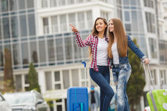 Two girlfriends with suitcases awaiting departure at the airport. Beautiful girlfriend,two young women,a brunette with long straight hair,cute smile,dressed in Royalty Free Stock Image