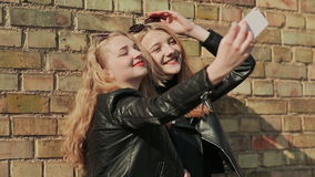 Two girlfriends in sunglasses and stylish leather jackets take a photo from a mobile phone near a brick wall on the. Street stock footage