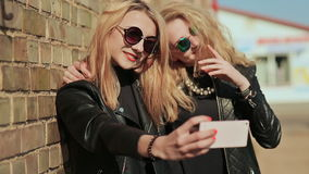 Two girlfriends in sunglasses and stylish leather jackets take a photo from a mobile phone near a brick wall on the. Street. Do selfie stock video