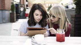 Two girlfriends with a tablet in an outdoors cafe. Technology and social media stock footage