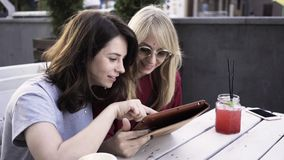 Two girlfriends with a tablet in an outdoors cafe. Two girlfriends are sitting in an outdoors cafe on a summer day and web surfing from a digital tablet stock video