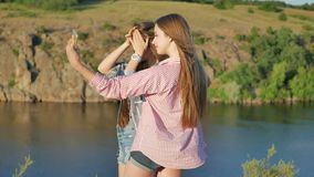 Two girlfriends taking photos in park. Girls selfie outdoor. Young women posing on phone camera stock footage