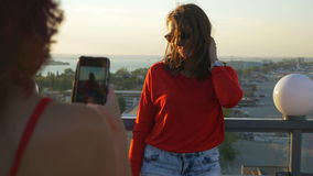 Two girlfriends taking photos with smartphone on the rooftop stock video