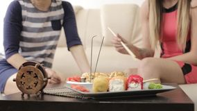 Two girlfriends talking during dinner at the restaurant, eating rolls with chopsticks.  stock video
