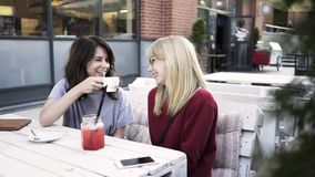 Two girlfriends talking and drinking coffee in an outdoors cafe. Two young friends are sitting in an outside cafe and having a lively conversation. A dark haired stock video footage