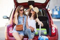 Two girlfriends talking, sitting in open car trunk Stock Image