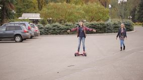 Two girlfriends teenagers have fun. girl drives on an electron gyroscooter in the park. Two girlfriends riding on an electronic scooter in an autumn park stock video