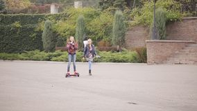 Two girlfriends teenagers have fun. girl drives on an electron gyroscooter in the park. Two girlfriends riding on an electronic scooter in an autumn park stock footage