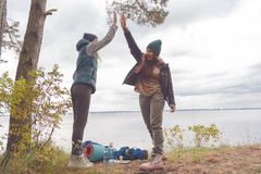 Two girlfriends travelers are proud of themselves and gave each other a high five. The concept of team success. Two girlfriends travelers are proud of Stock Photography