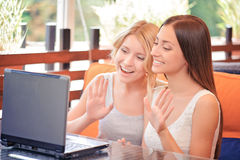 Two girlfriends using laptop in cafe Stock Photo