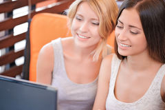Two girlfriends using laptop in cafe Royalty Free Stock Photos