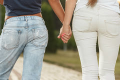 Two girlfriends are walking in the park. Two girlfriends are walking with holding hands in the park Stock Images