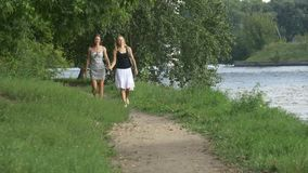 Two girlfriends walking in the park holding hands stock video
