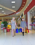 Two girlfriends walking with shopping bags Royalty Free Stock Image