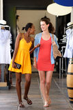 Two girlfriends walking and talking at shopping mall Stock Photos