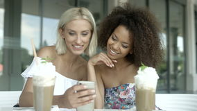 Two girlfriends watching photos on phone and smiling. stock video footage