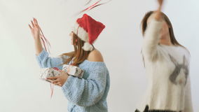 Two girlfriends waving a red ribbons and dances with gifts at white background. Two pretty girlfriends with festive gifts dances at white background and waving a stock video footage