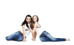 Two girlfriends wearing blue jeans isolated Royalty Free Stock Images