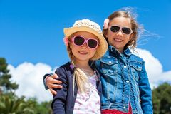 Two girlfriends wearing sunglasses outdoors. Stock Photography