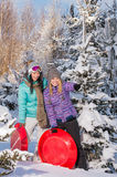 Two girlfriends in winter snowy forest bobsleigh Royalty Free Stock Image