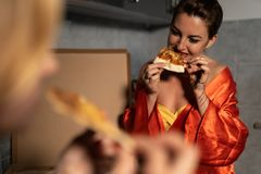 Two girlfriends women eating pizza and enjoying an evening party chat before going out - One wearing blue morning gown stock image