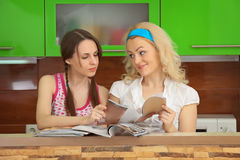 Two girlfriends with women's magazines on kitchen Stock Photo