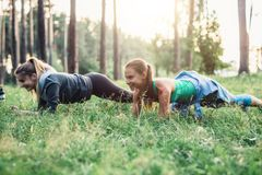Two girlfriends working out outdoors doing plank exercise on grass.  royalty free stock images