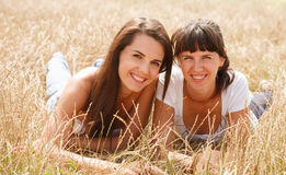Two girlfriends. Two young women lying down in grass smiling looking at camera Royalty Free Stock Image