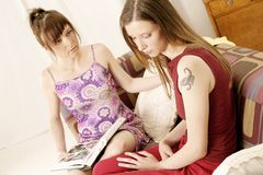 Two girls. Young women sitting on a sofa and watching photo-album Royalty Free Stock Photos