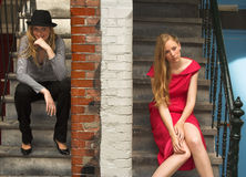 Two girls. Sitting at neighbor house entries, separated by the wall stock image