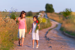 Two girls. Walking along the road with a bouquet of flowers Royalty Free Stock Photo