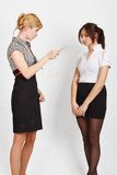 Two girls. Two female students. One student is explaining something to another Stock Image