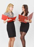 Two girls. Two cute female students reading the documents and smiling Royalty Free Stock Photos