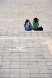 Two girls. Sitting at a plaza in Puerto Cruz Royalty Free Stock Image