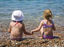 Two girls. Sitting on the shore of sea Royalty Free Stock Photos