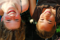 Two girls. Hanging upside down in a playground Stock Photo