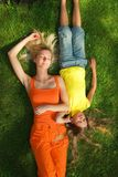 Two girls. Lying on a green grass Royalty Free Stock Images