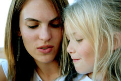 Two girls. Close head portrait of two caucasian girls with concentrating facial expression looking down Stock Images