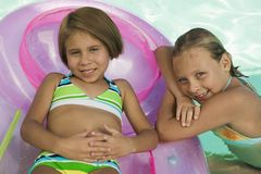 Two girls (7-9) in swimming pool royalty free stock photo