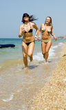 Two girls. Running on background of the sea Stock Images