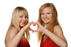 Two girls with the abstract form of heart. Made by hands. It is isolated on a white background. Selective focus Stock Photo