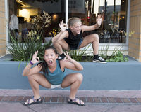 Two girls acting crazy. A thirteen year old teenage girl is squatting in a deep knee bend and her twelve year old Amerasian cousin is also squatting.  They both Royalty Free Stock Photo