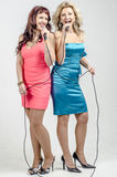 Two Girls actress singer in cocktail dresses with microphones blonde and brown hair Stock Image