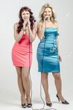 Two Girls actress singer in cocktail dresses with microphones blonde and brown hair Royalty Free Stock Images