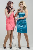 Two Girls actress singer in cocktail dresses with microphones blonde and brown hair Stock Images