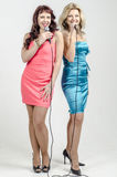 Two Girls actress singer in cocktail dresses with microphones blonde and brown hair Royalty Free Stock Photos
